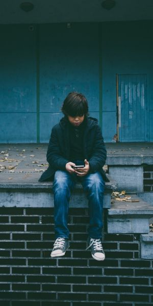 Child sitting outside with a phone