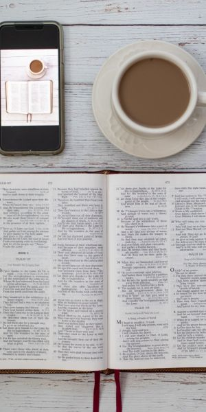 Tablescape of an open Bible, smart phone and hot drink