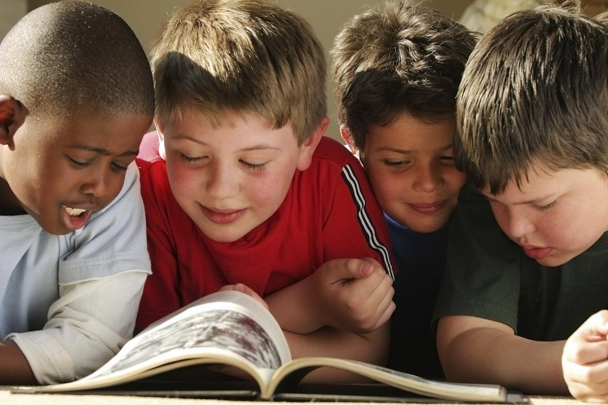 SCHOOL BOYS READING A BOOK TOGETHER