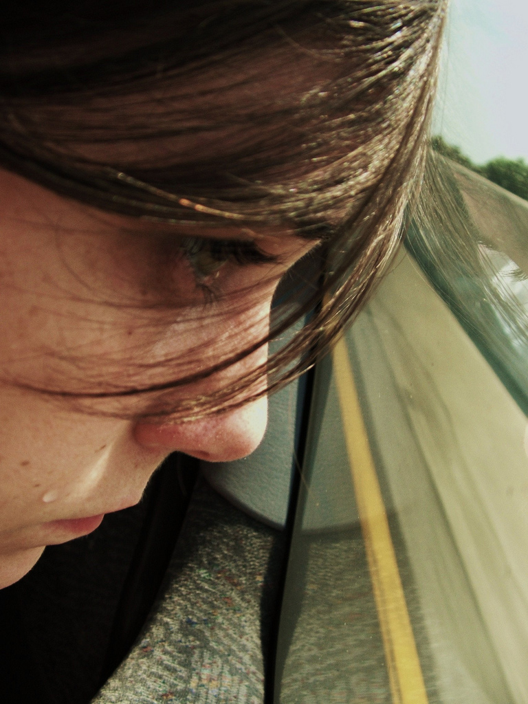Young girl crying with her head looking out of the window of a moving car