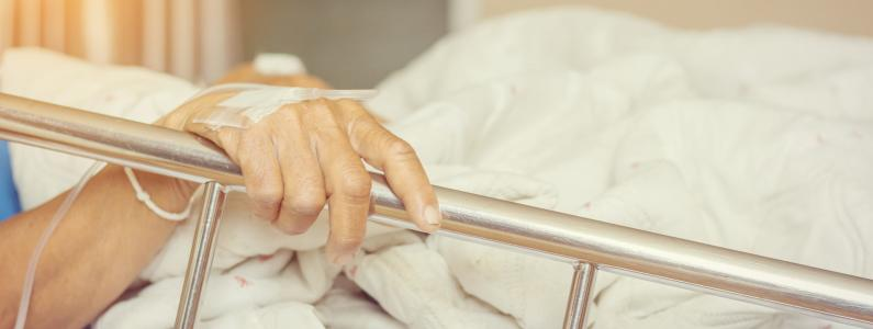 hand on rail of hospital bed