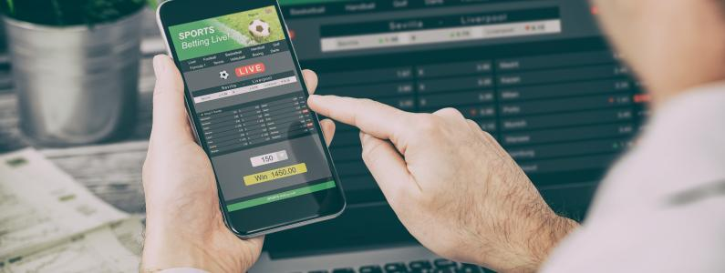 man with phone looking at screen and placing a bet
