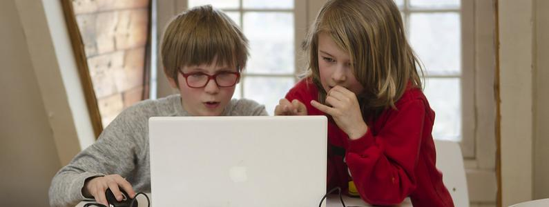 boy and girl on a laptop at home