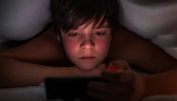 young boy watching ipad under duvet cover