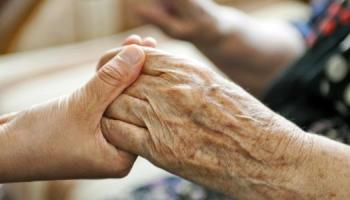 hands held together, one elderly person and the other a carer