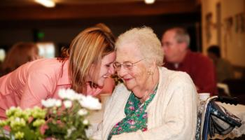 Elderly lady visited by young lady, heads together with smiles