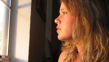 blonde woman looking out of a windo
