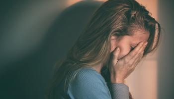 blonde woman crying into hands