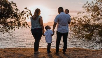 family of four looking out at sunset