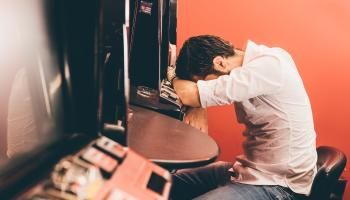 man with head in his hands at betting machines