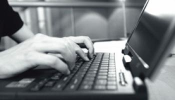 A black and white image of a person typing on a laptop