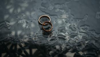 Two wedding rings in pool of water with dark background