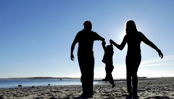 Silhouette of a mother and father lifting their child off the ground by the hands on a beach