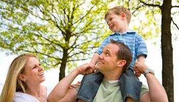 Smiling mother and father with little boy on his shoulders laughing