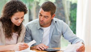 husband and wife looking at finances on table with calculator and papers