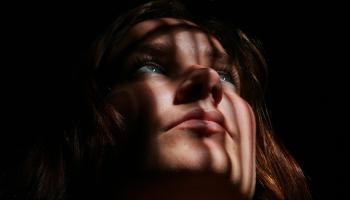 woman looking up out of darkness with reflection of prison bars on her face
