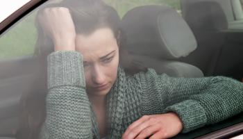 A troubled woman trapped inside a car, she is staring out of the window with her head leaning on palm of her right arm