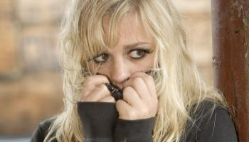 blonde woman looking cold and afraid, pulling jumper up to cover mouth