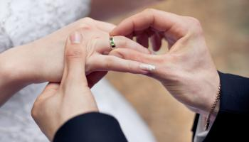 picture of a groom putting a wedding ring on a bride