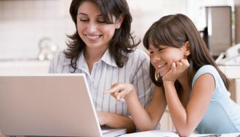 daughter smiling at laptop with mother and pointing at screen