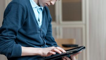 Boy leaning on table using ipad