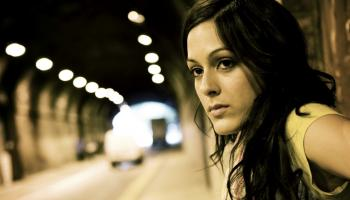 Young woman leaning against tunnel wall and looking out at vehicles driving by