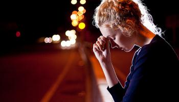 Woman on side of road at night, with hand to her forehead looking down as car approaches