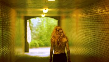 Young woman walking through tiled underpass in daytime
