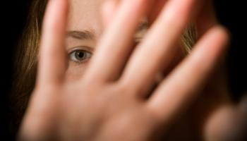 woman's face close up with hands infront trying to push away and eyes looking through hands