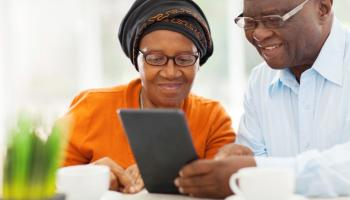 couple smiling, looking at tablet