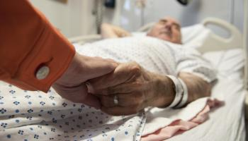 man lying in hospital bed holding hand of lady