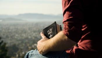 man holding bible witting outside looking at view
