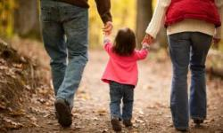 Two adults walking with a child in between them all holding hands