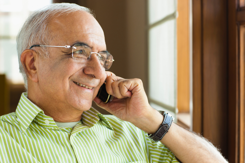 man smiling, on the telephone, looking out of the window